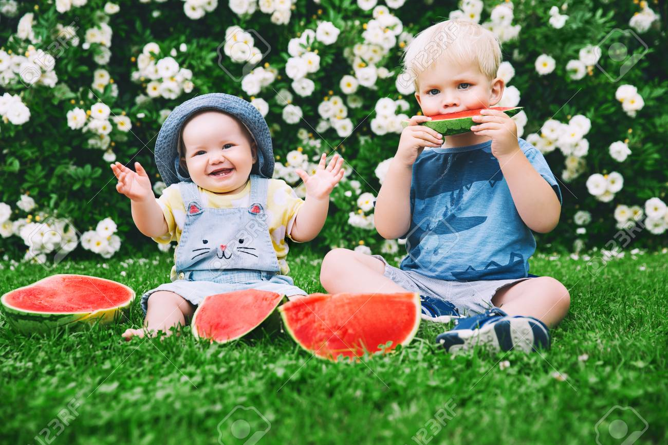 funny little kids eating watermelon on green grass on nature at