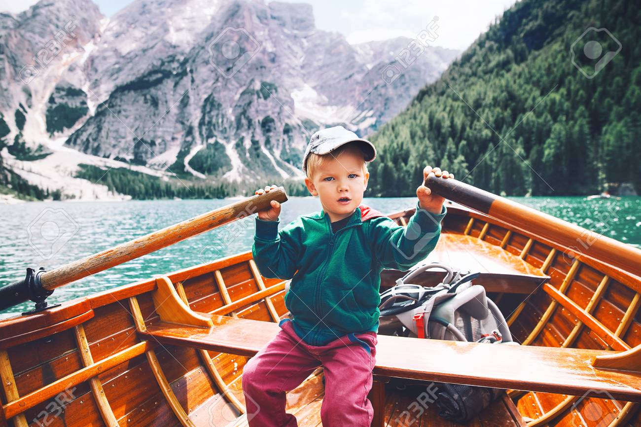Funny Child With Family On Walk By Traditional Wooden Boat With Oars