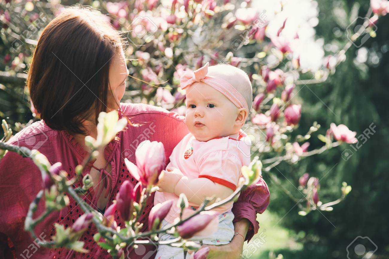 Loving Mother And Baby Girl Are Smelling Blooming Blossom Pink