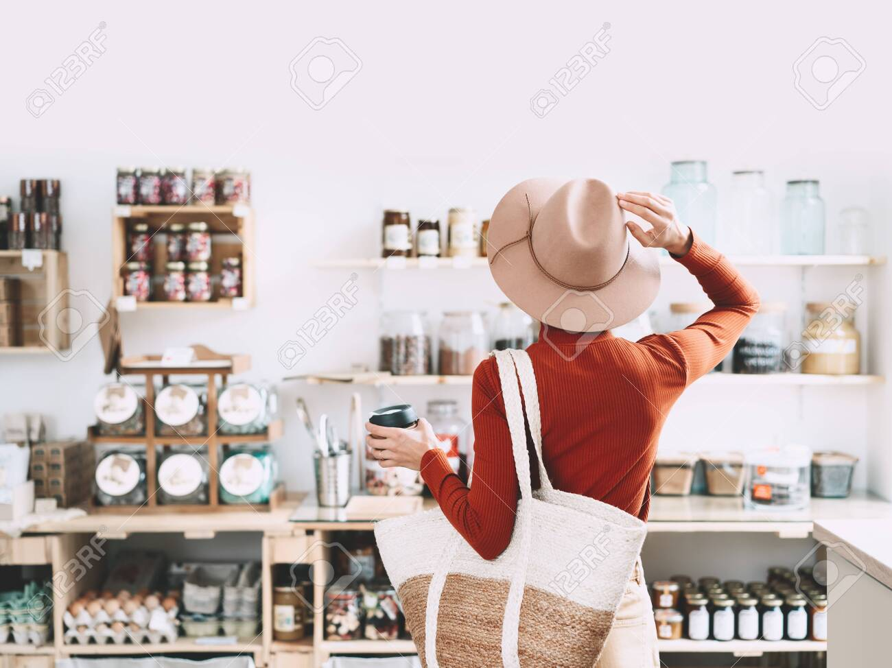 Minimalist vegan style girl with wicker bag and reusable glass coffee cup on background of interior of zero waste shop. Woman doing shopping without plastic packaging in plastic free grocery store. - 134621130