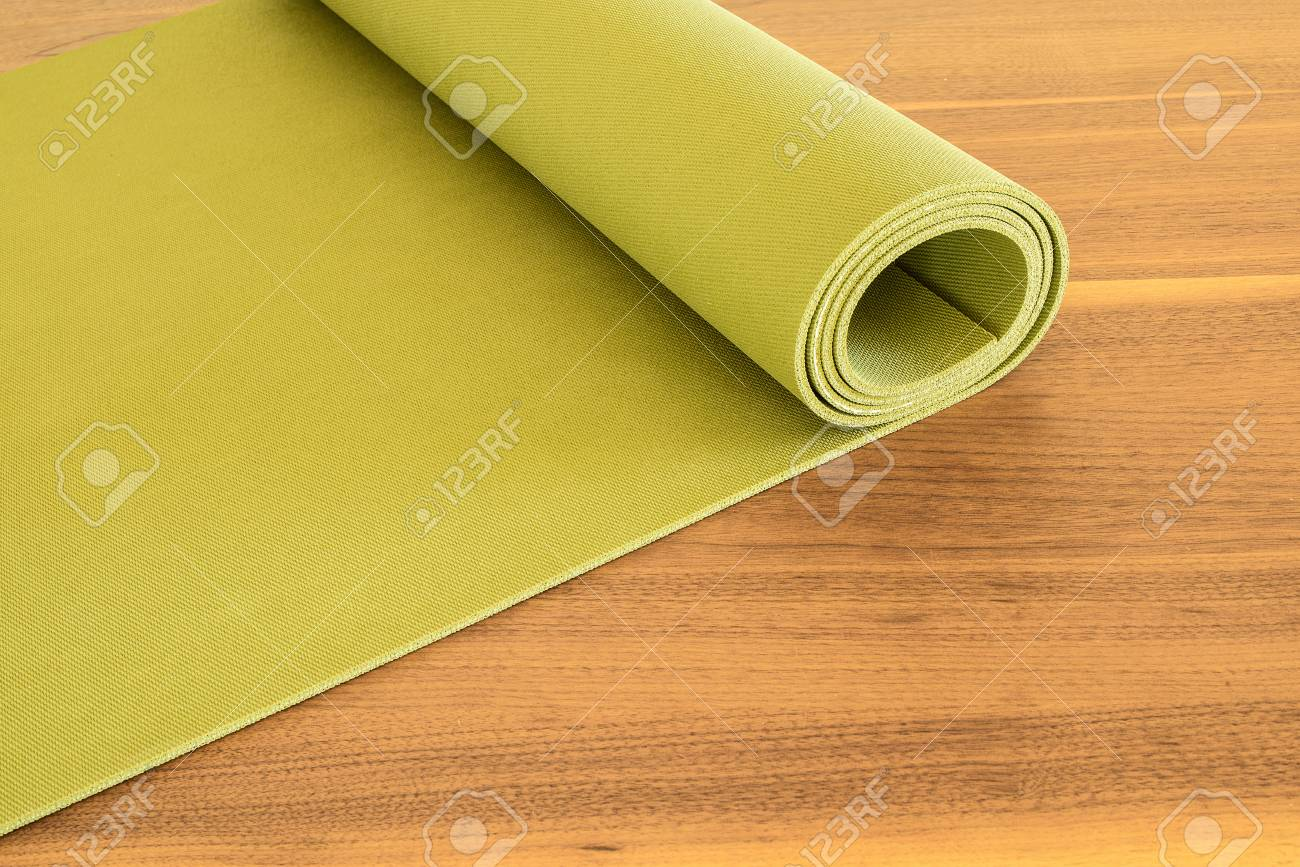 8e6d08301a549 Stock Photo - Yoga mat on a wooden background. Equipment for yoga. Concept healthy  lifestyle. Lots of copyspace