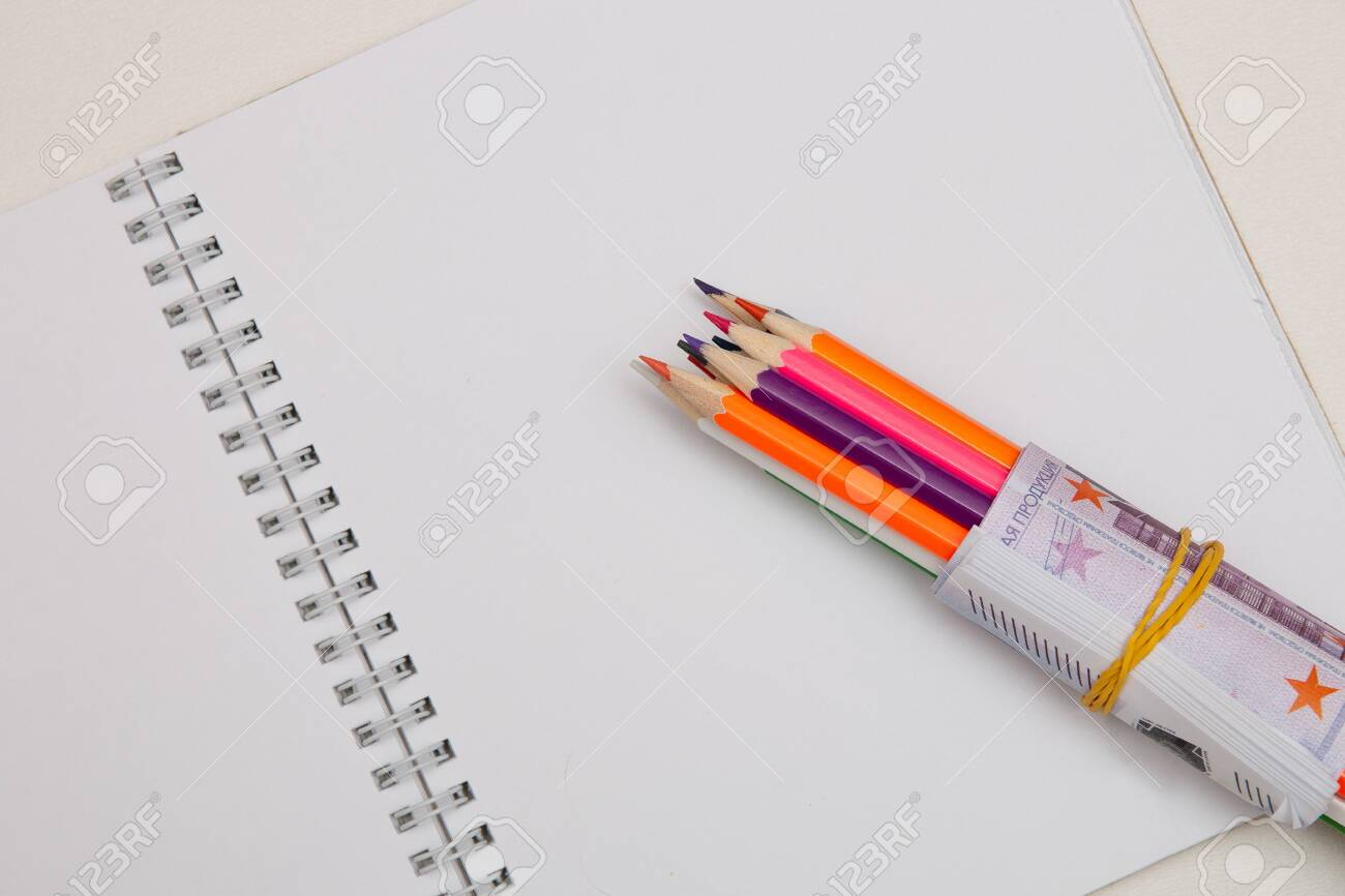 colored pencils wrapped in euro note lie on a white notebook on a white table bright copy space - 142601401