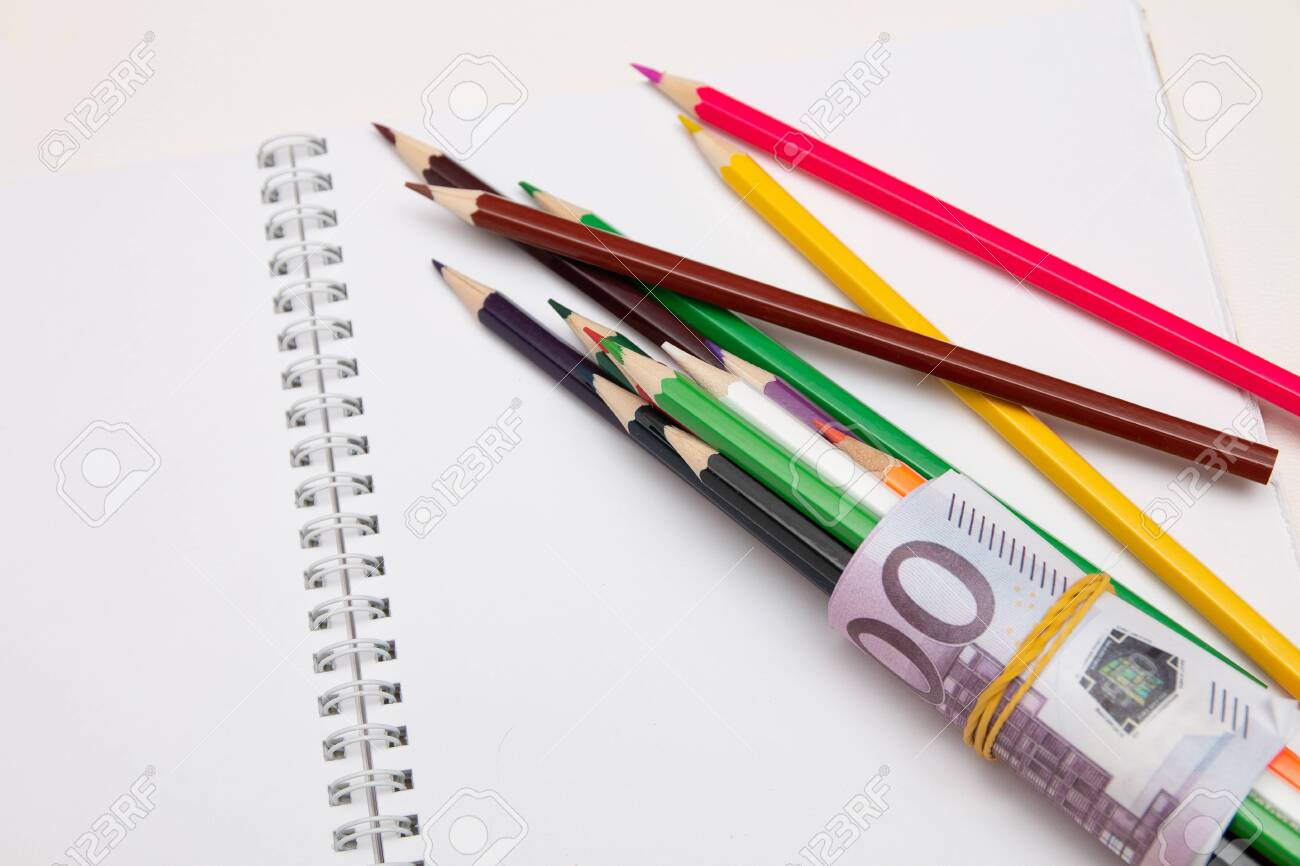 colored pencils wrapped in euro note lie on a white notebook on a white table bright copy space - 142566866