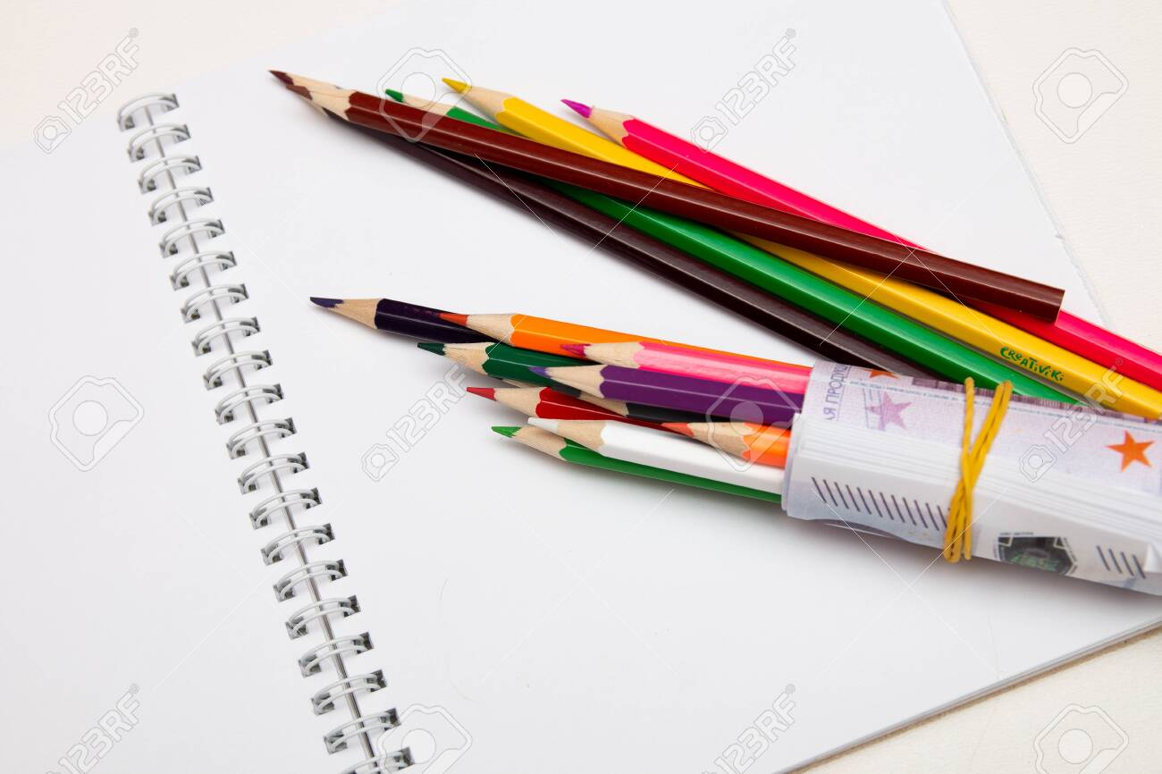 colored pencils wrapped in euro note lie on a white notebook on a white table bright copy space - 142602304