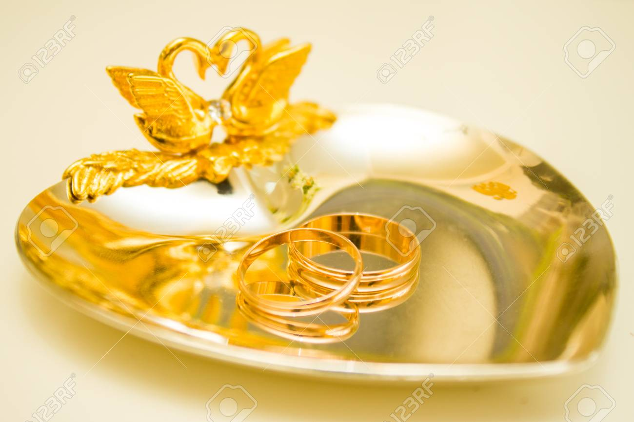 346f2c139d495 wedding symbols two rings on golden heart-shaped tray - love,..