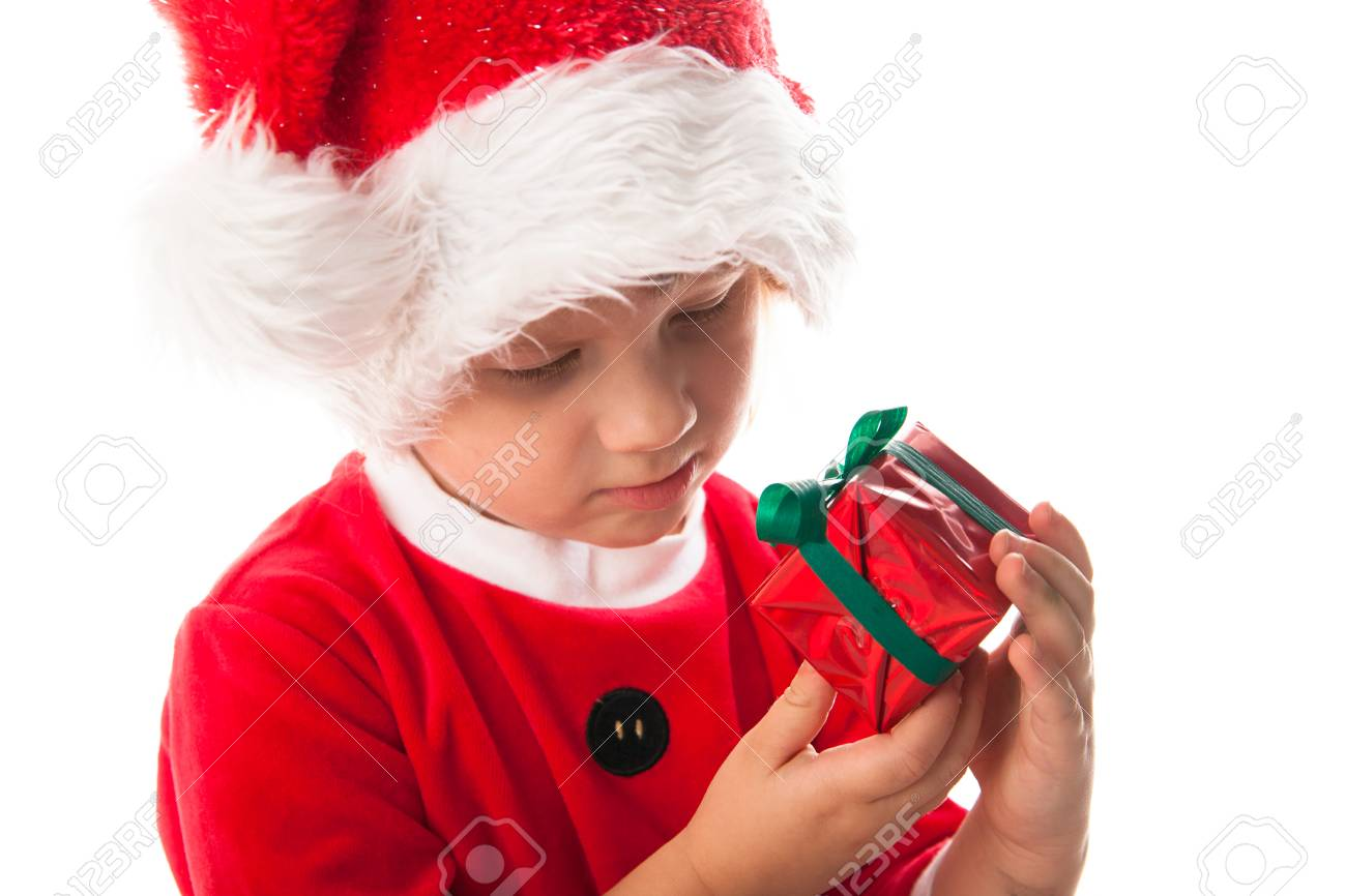 serious thoughtful child girl in santa red hat holding christmas gift in hands christmas