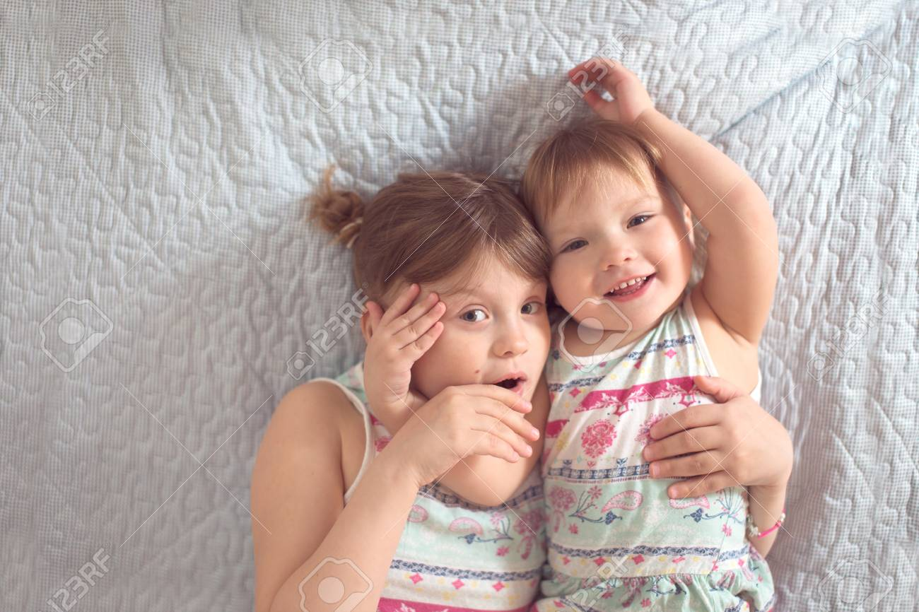 two cute siblings hugging and smiling on the bed light background