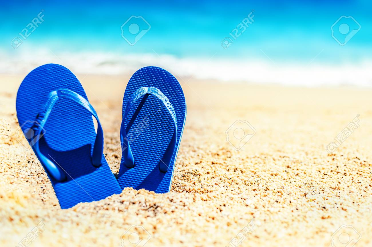 180da062d Stock Photo - Summer holiday beach background with flip flops on a tropical  beach. Slippers from a sand on a beach