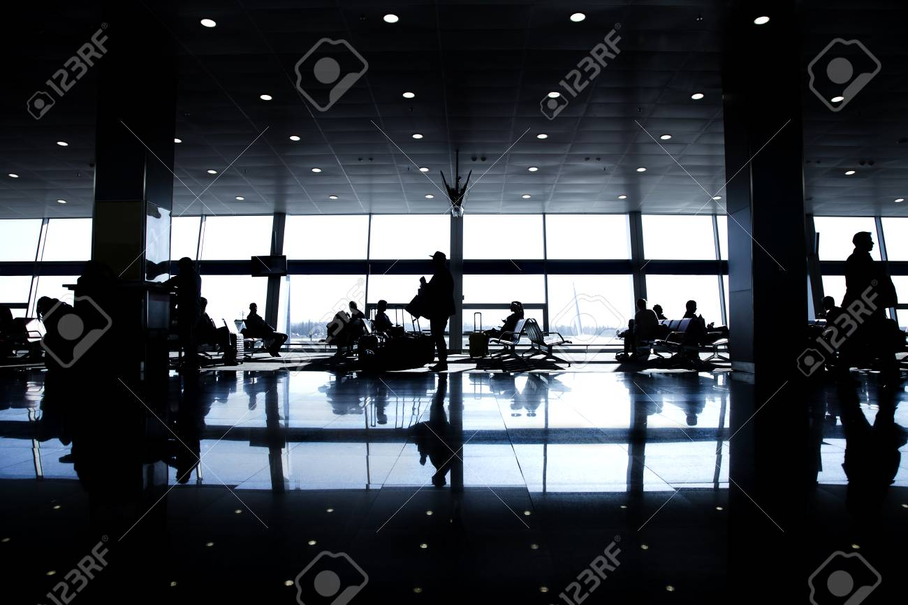 Silhouettes of passengers in a large airport in the background