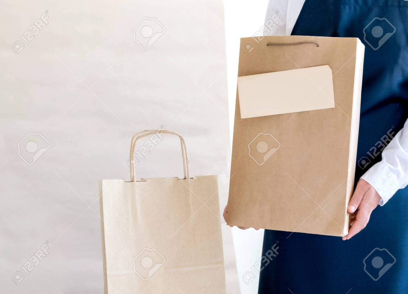A lot of Craft Paper Bags and Boxes stay near by Packer. Worker of Delivery Service in Uniform Packing Order for Customer. - 145911024