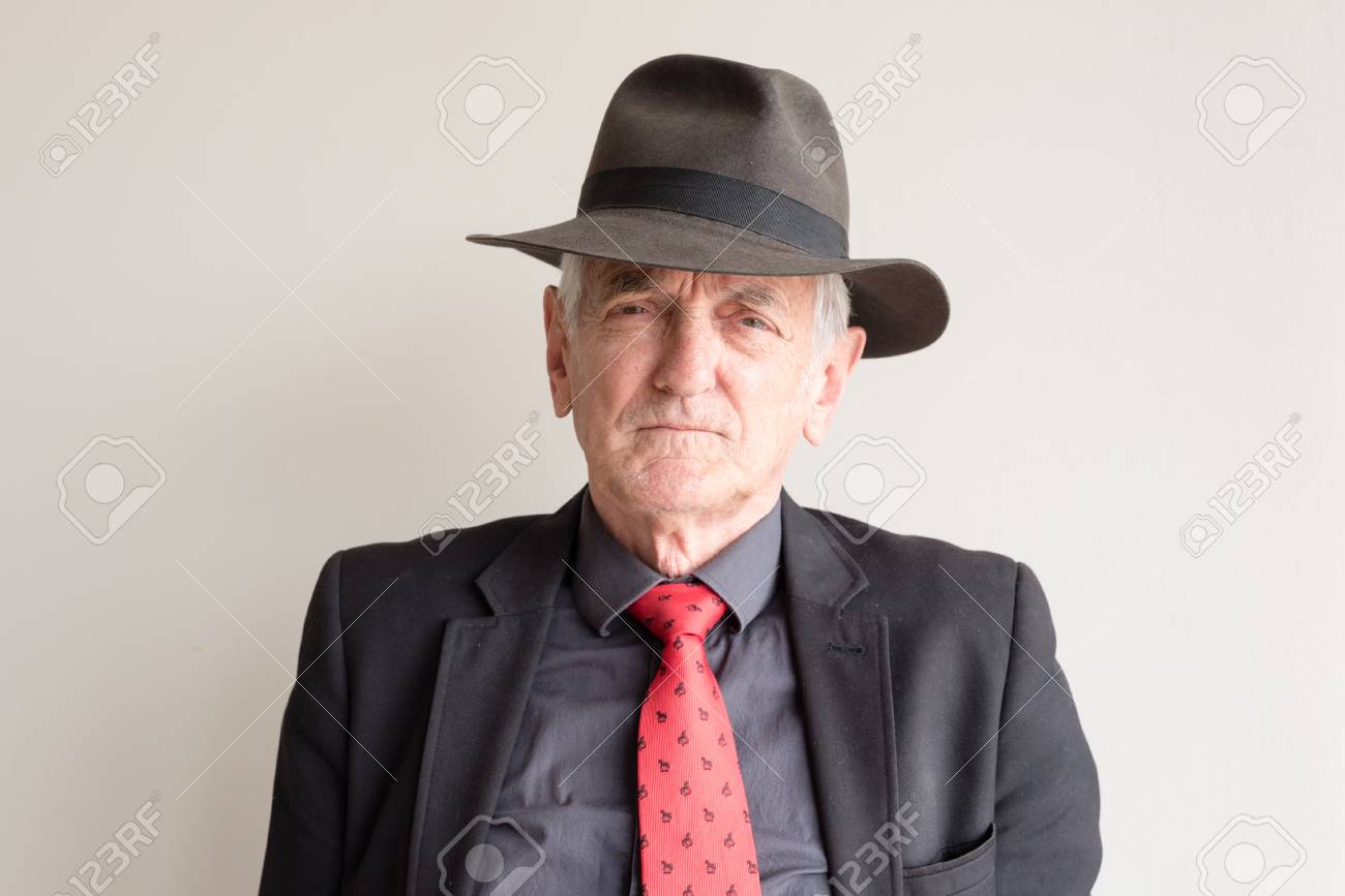 meilleur prix coupon de réduction pas mal Homme plus âgé habillé pour une journée aux courses de chevaux en costume  noir, cravate rouge et chapeau