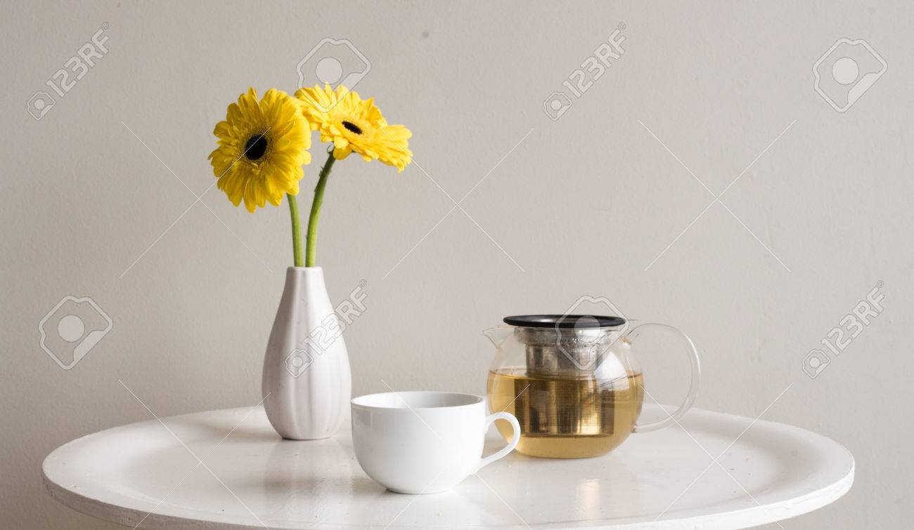 Small White Round Table With Cup, Glass Teapot Of Chamomile Tea And Yellow  Gerberas In