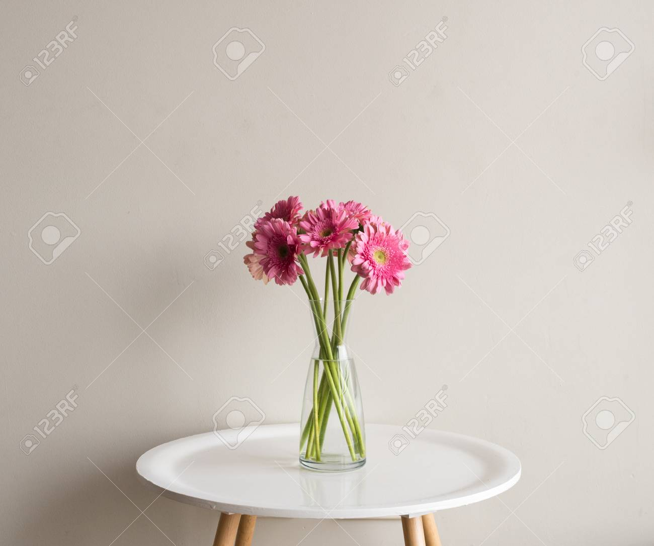 Pink Round Table.Pink Gerberas In Glass Vase On Small White Round Table Against