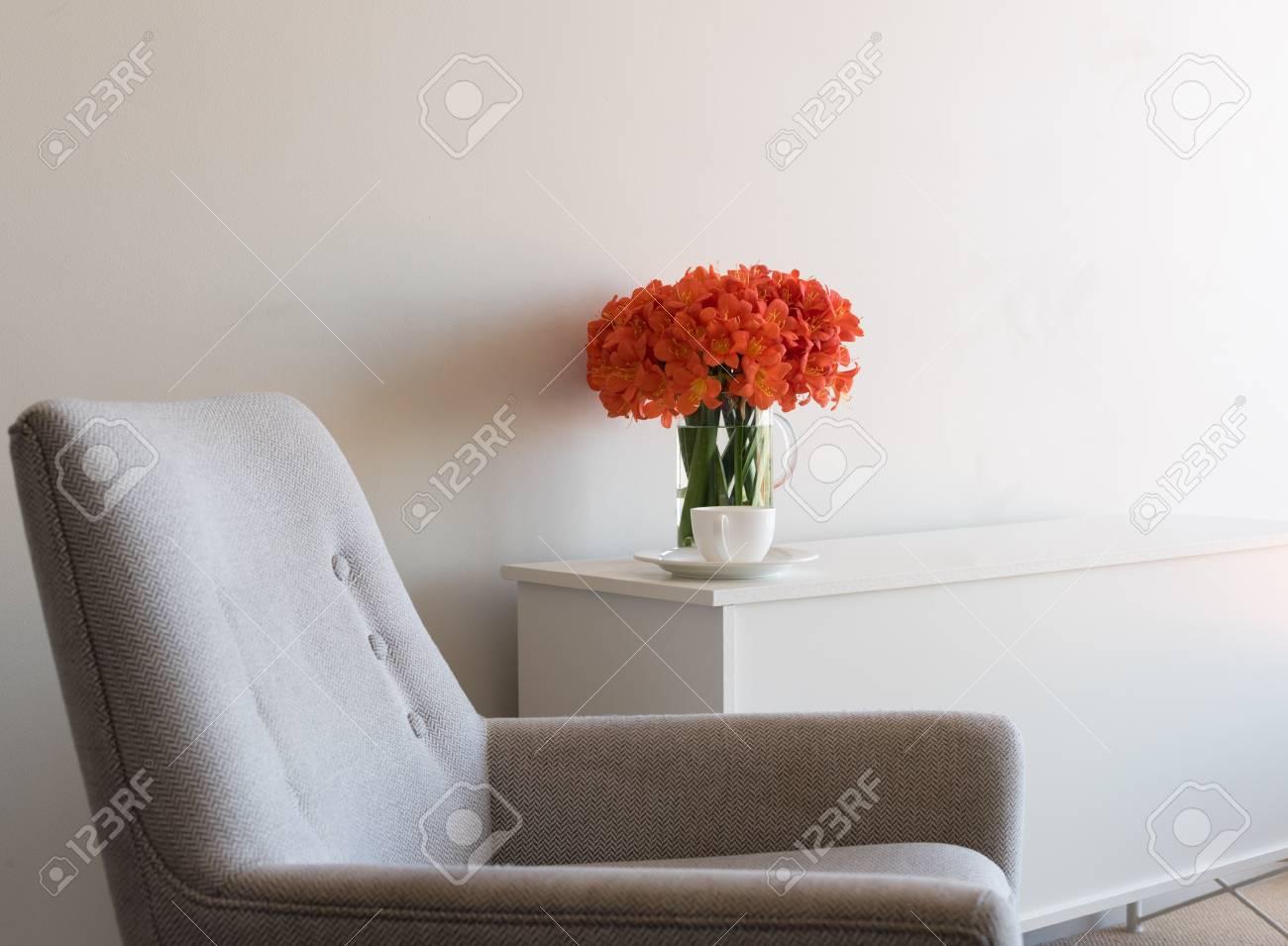 Credenza Moderna Arancione : Poltrona retrò con credenza bianca tazza da tè e fiori clivia