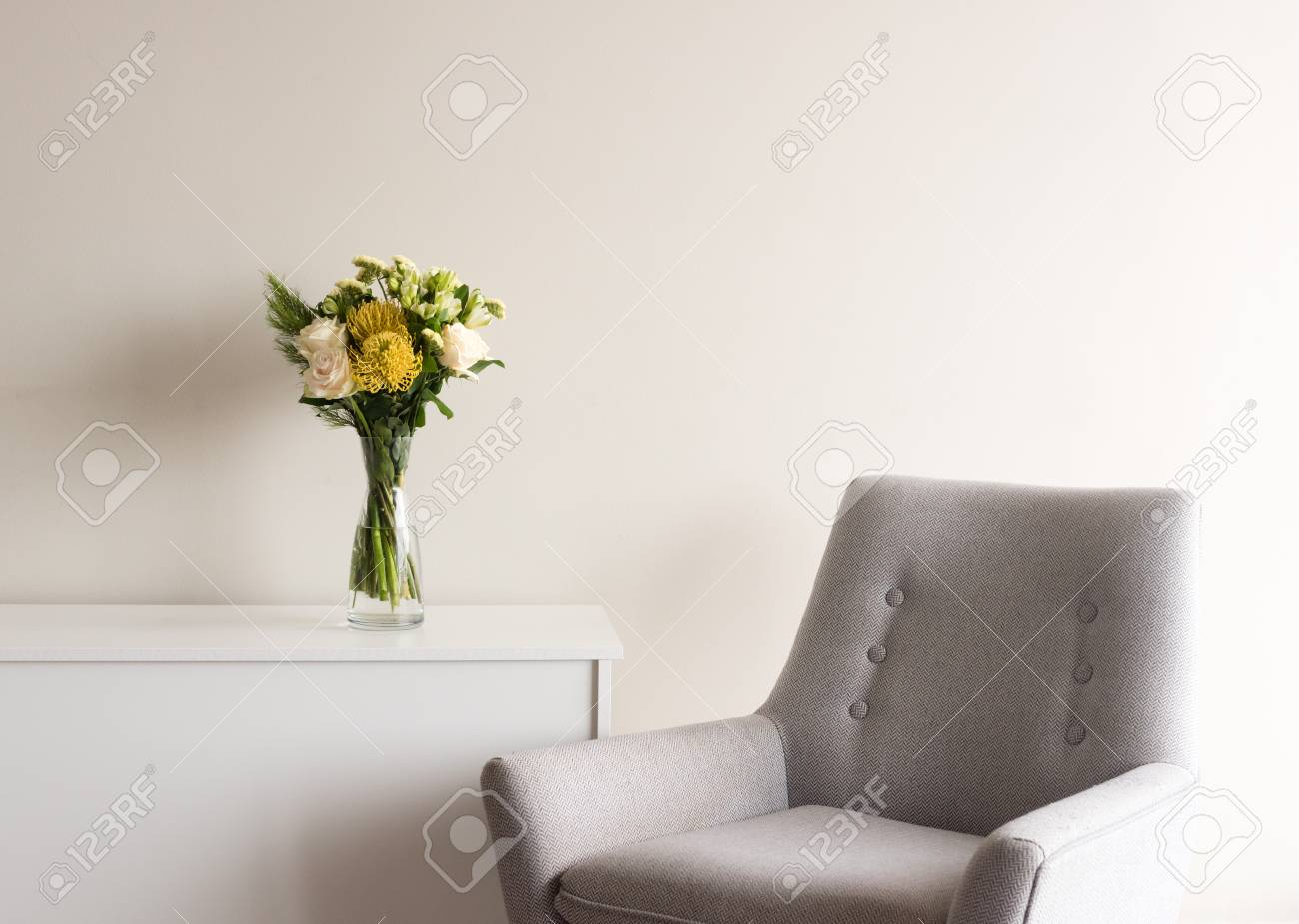 Close Up Of Grey Retro Armchair Next To White Cabinet With Cream