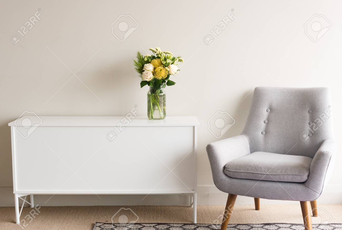 photo grey retro armchair next to white sideboard with glass jar of cream and yellow flowers against neutr