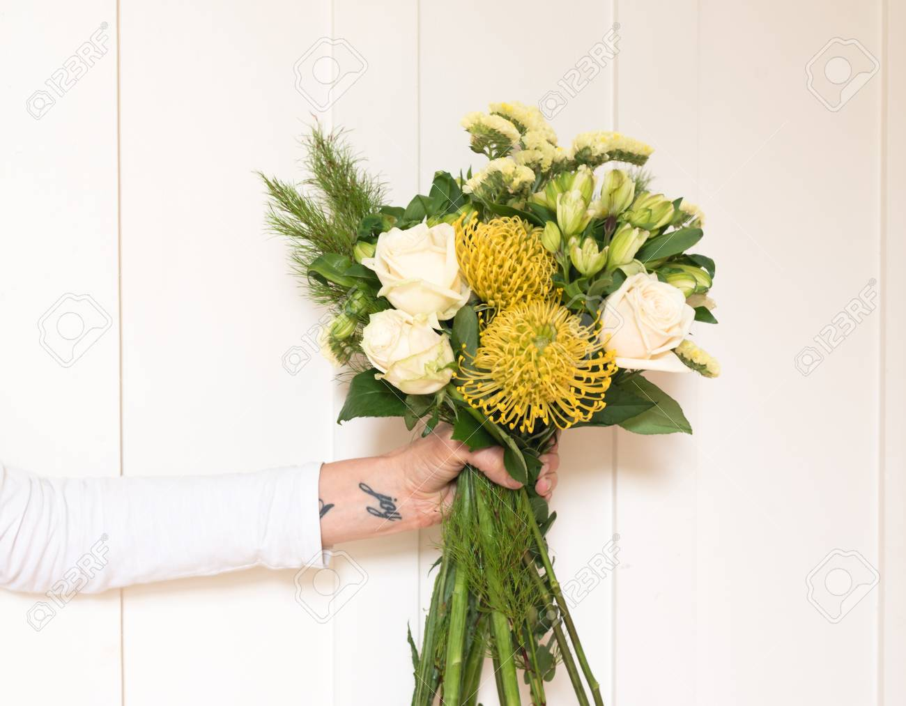 Womans Arm Holding Bouquet Of Cream And Yellow Flowers Against