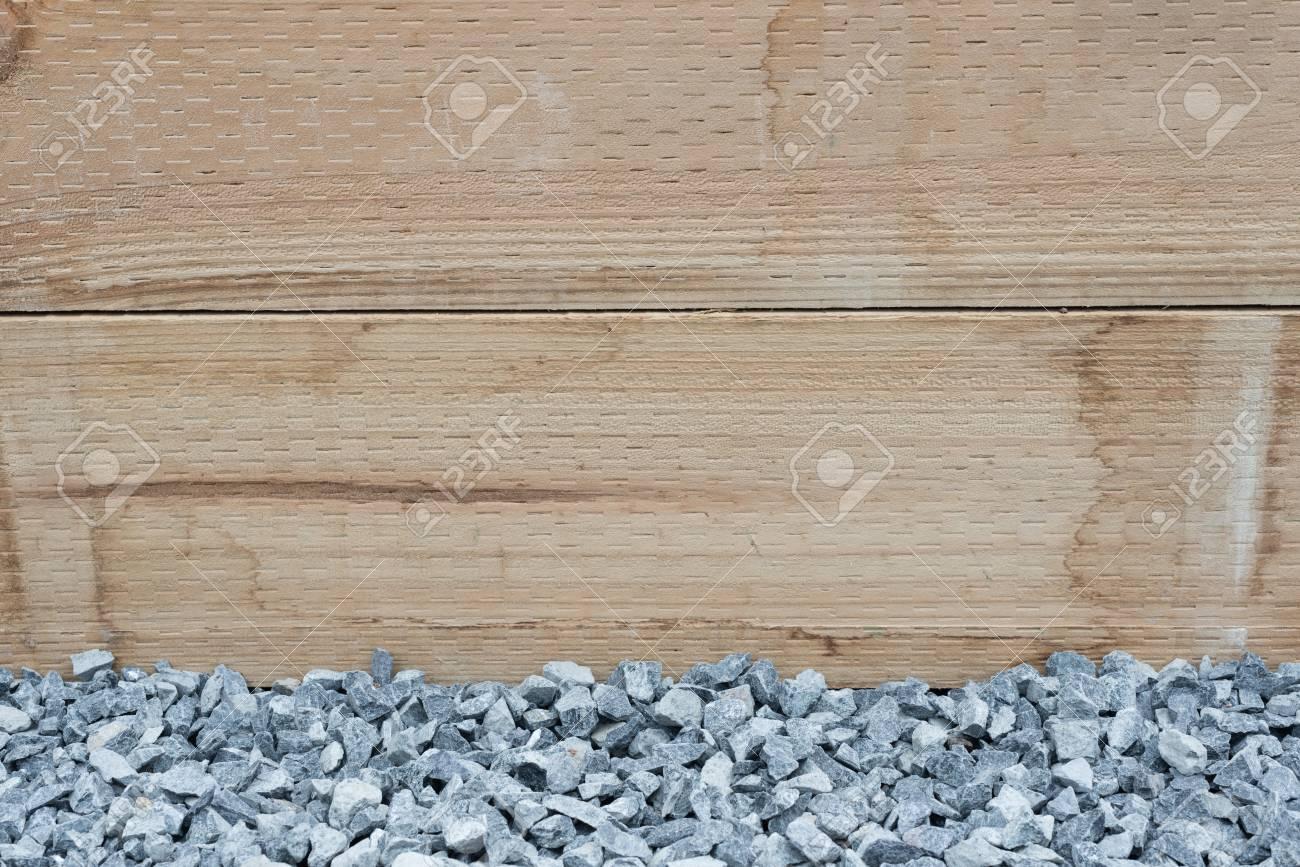 Closeup of bluestone gravel against treated pine retaining wall