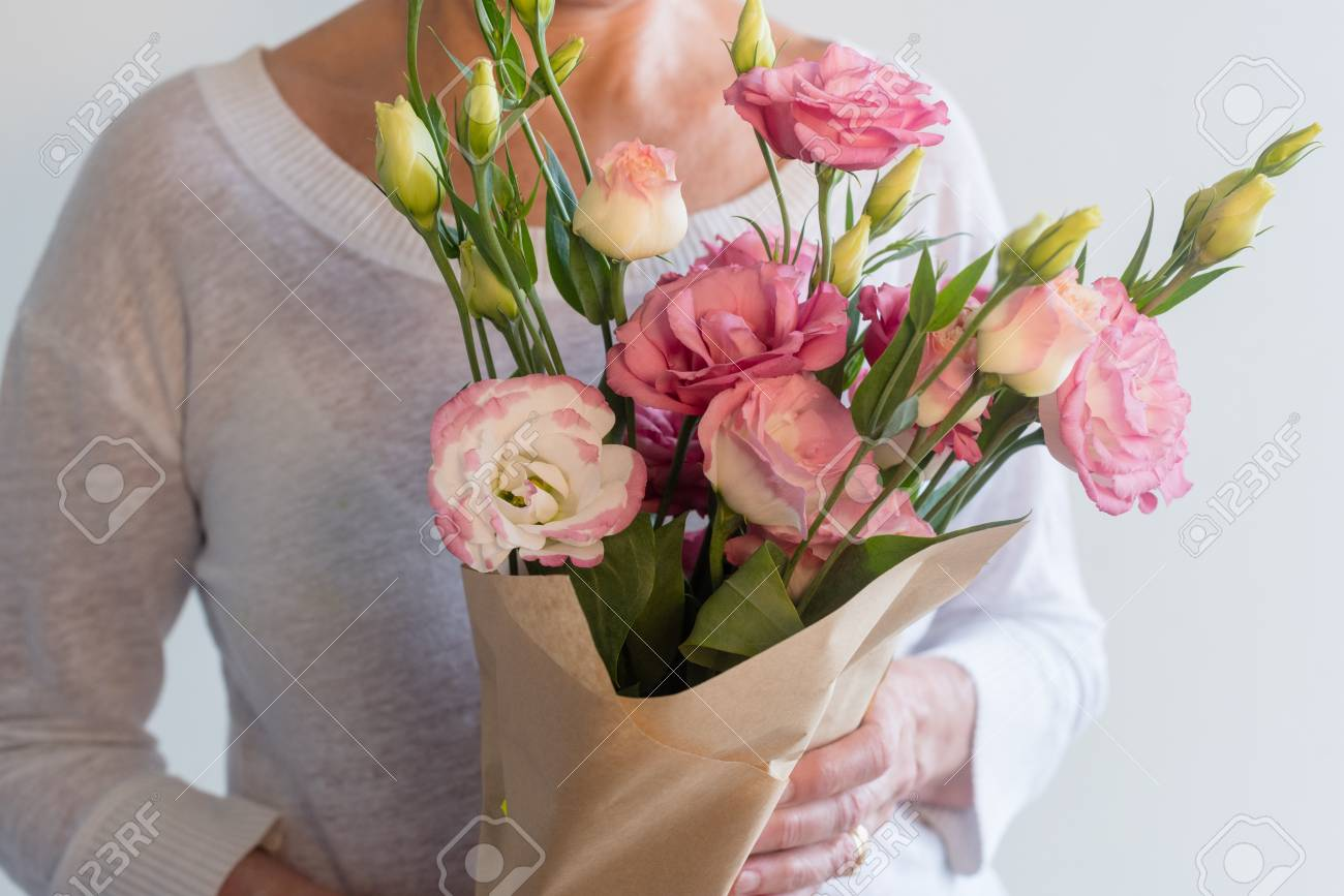 Close up of woman holding bouquet of pink lisianthus flowers stock close up of woman holding bouquet of pink lisianthus flowers wrapped in brown paper selective mightylinksfo