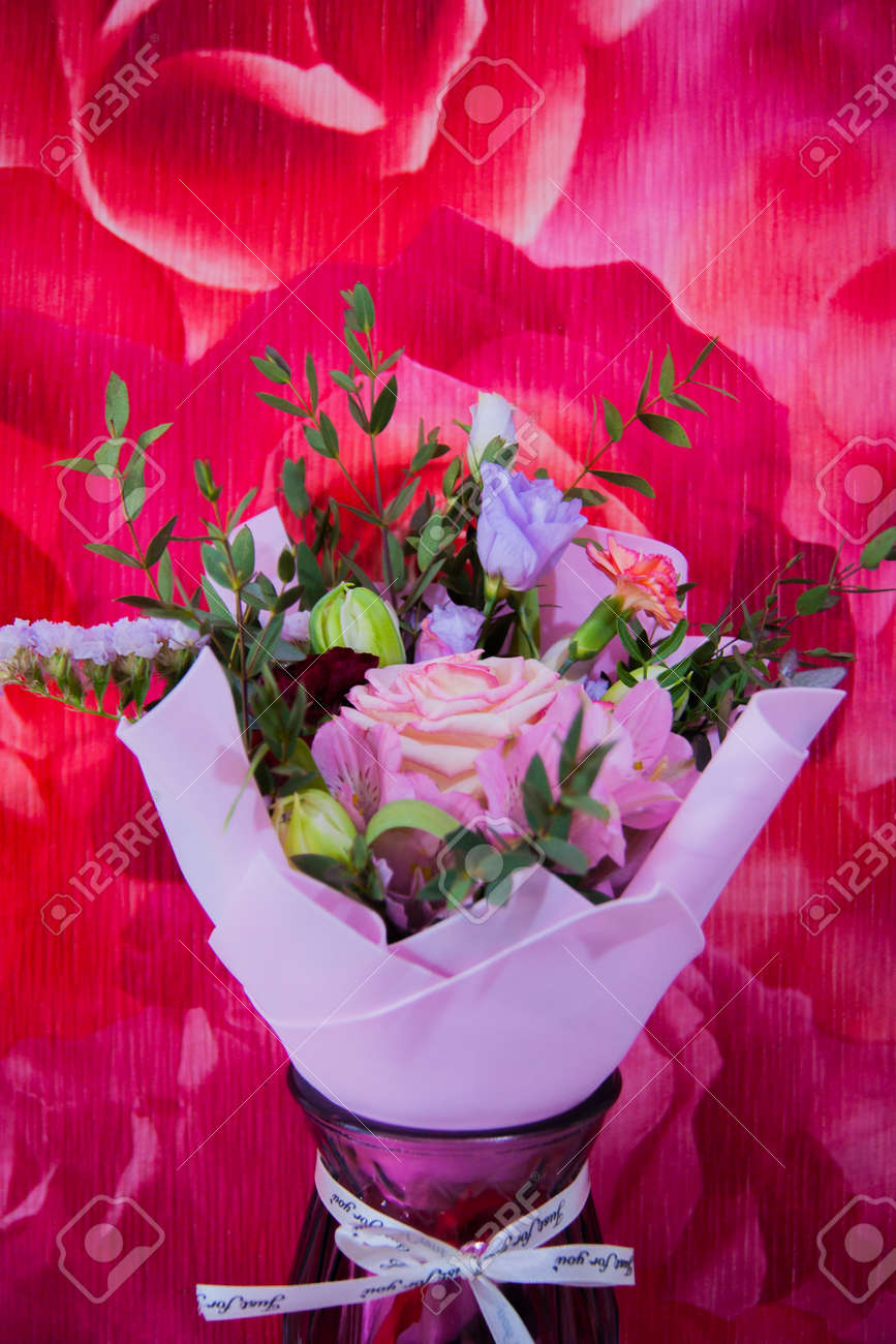 A delicate bouquet of different flowers in a light pink wrapper stands against a colorful pink wall in a home setting. Vertical photo. - 167836010