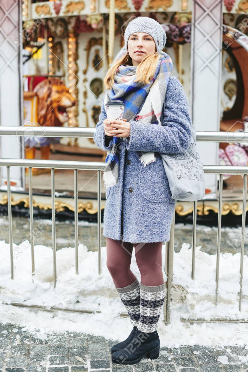 outlet f05f8 ff56c Ragazza in cappotto grigio, cappello e sciarpa coperta con tazza di caffè  vicino a carosello, stile di vita stile di strada invernale