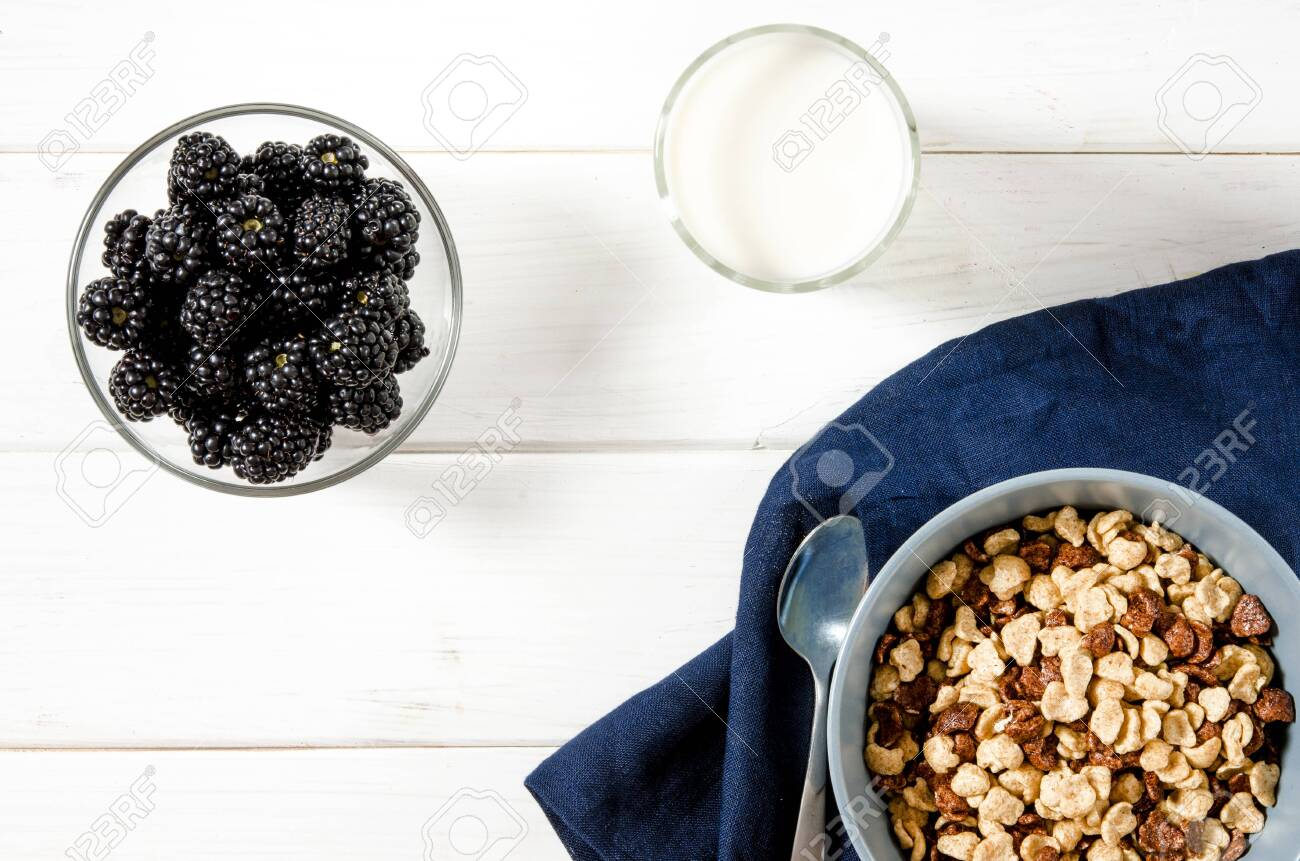 Healthy food: a healthy breakfast of cornflakes and blackberry berries on a white tree table. top view - 128126692