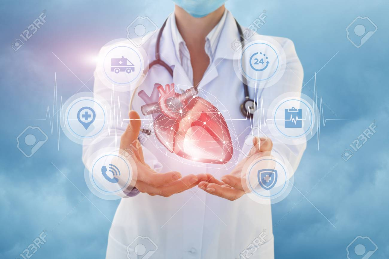 Health worker shows a heart in hands on sky background. - 88022257