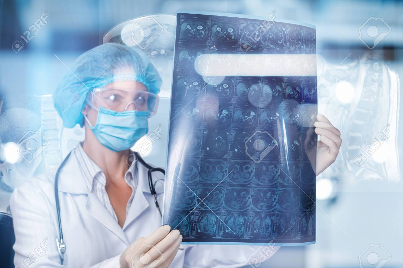 A doctor is examining a magnetic resonance imaging scan on a blurred background. - 128328557