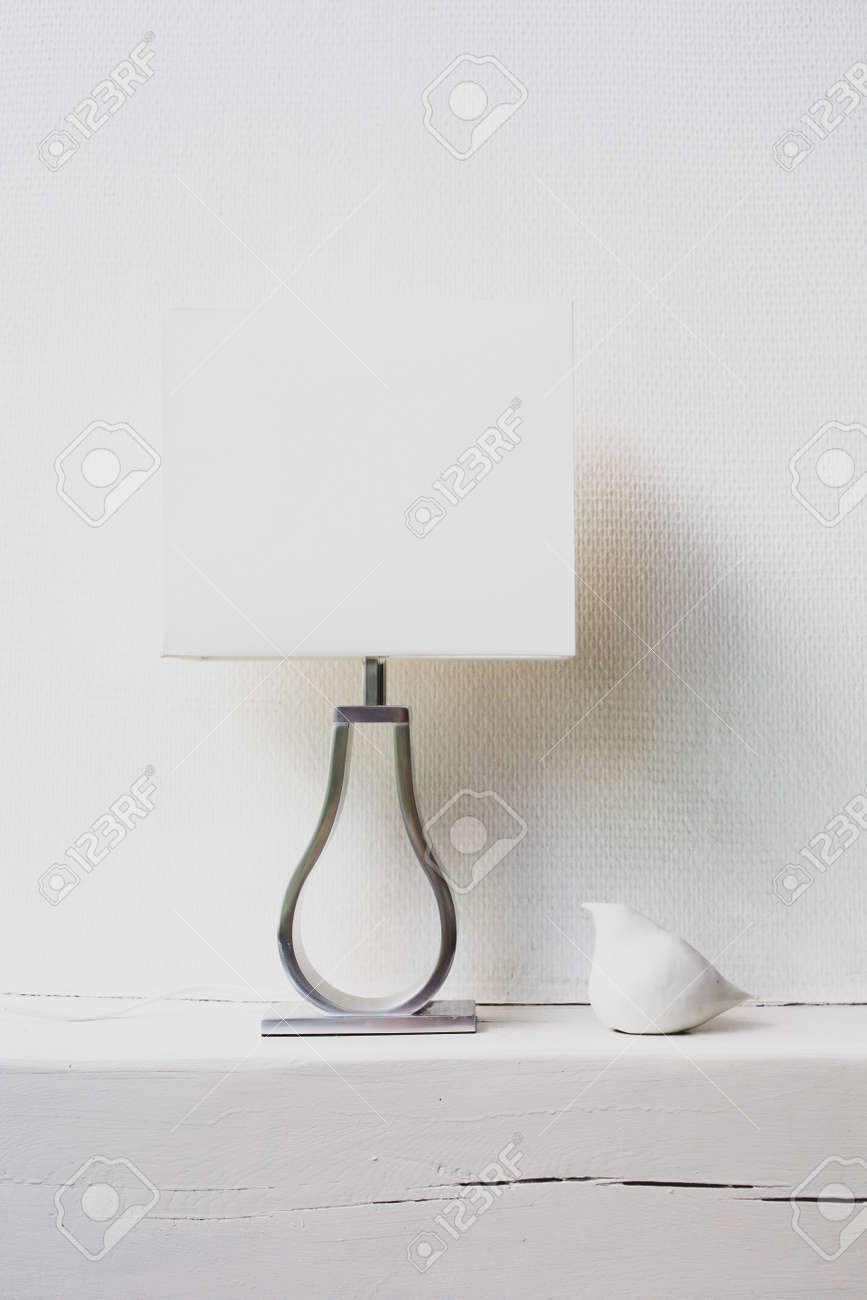 A white lamp and a sculpture of a white bird are on a shelf in the house against the background of a white wall. - 158031326