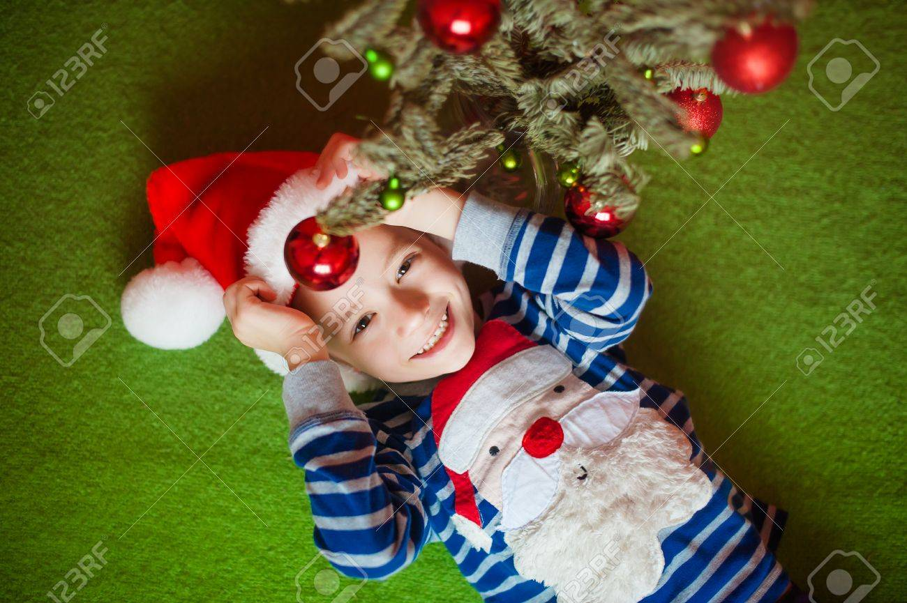 13060f5b5 ... with Santa Claus. Happy little boy is lies near fir-tree on a green  blanket. New Year's