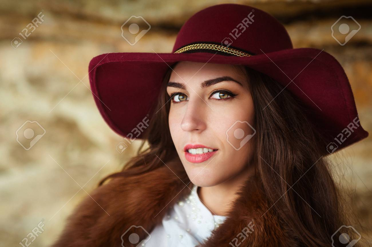 9f5eca166a20 Beautiful girl in maroon felt hat close up portrait. Outdoor shoot. look at  the