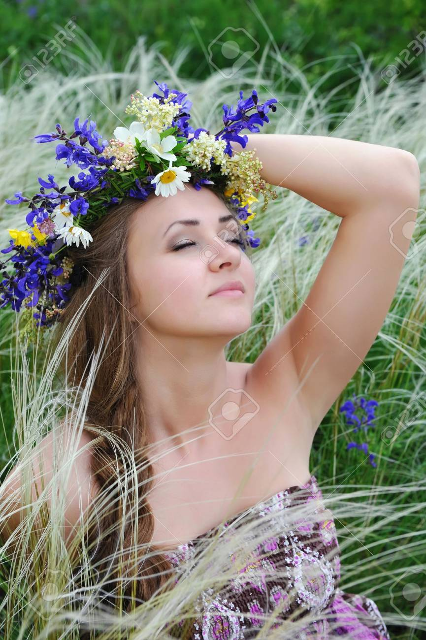 Beautiful Young Woman With Flower Wreath In The Grass Of Feather Grass