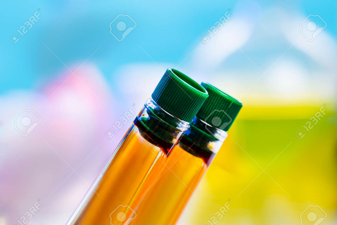 Two chemical test tubes with closed lids with orange liquid on a blue background. Urine test, delivery of urine, - 166481692