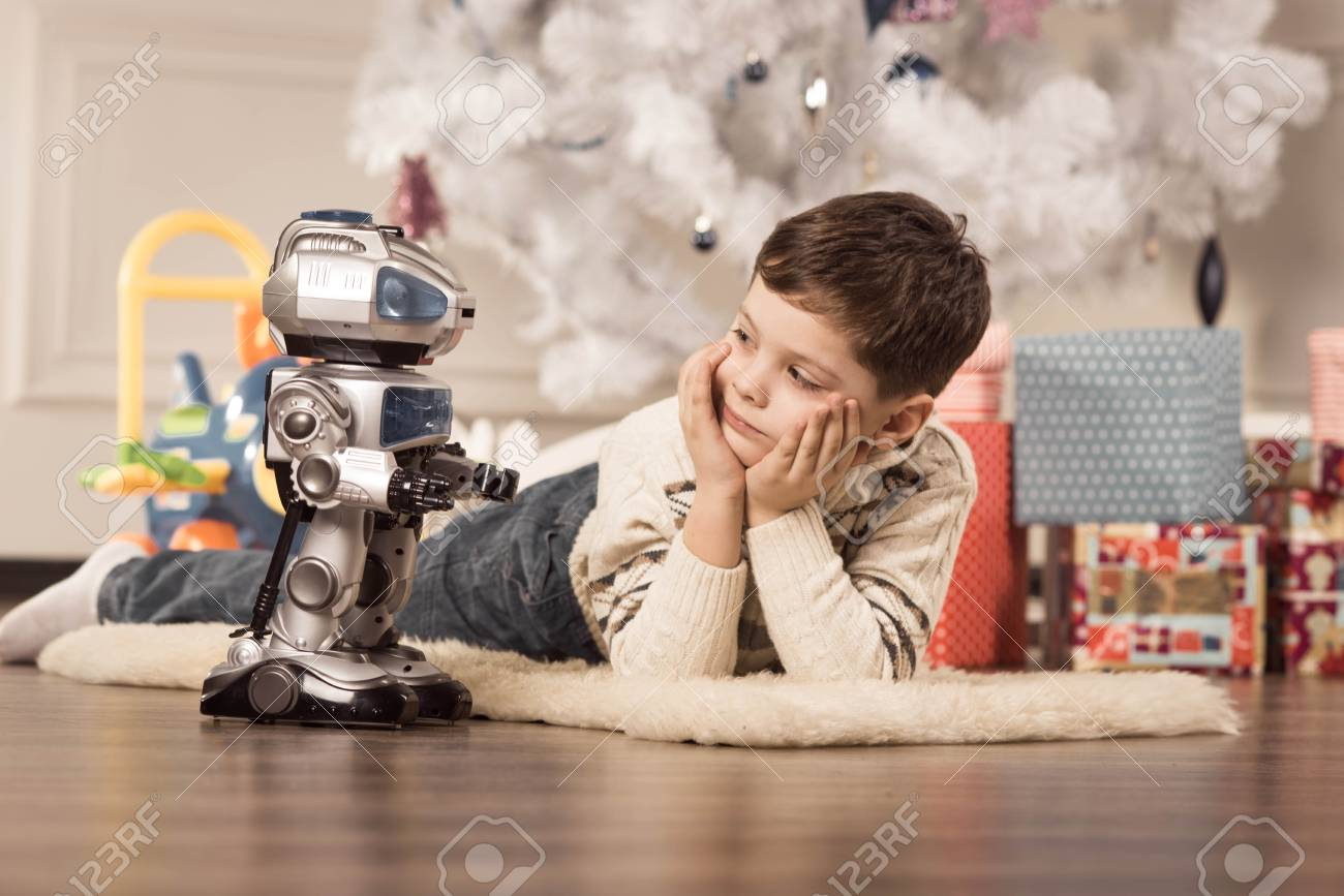 Boy with Christmas gifts under the tree - 36497905