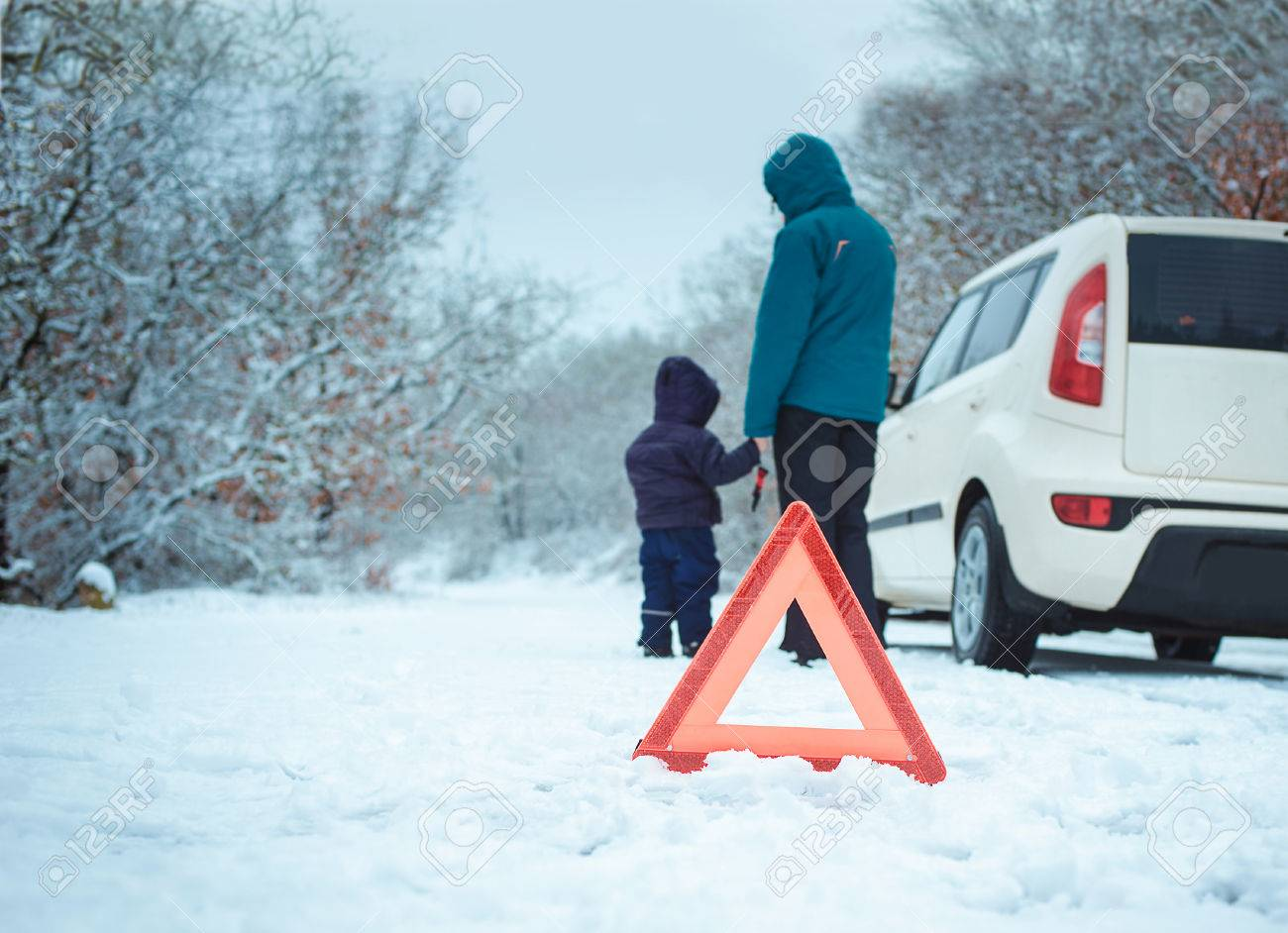 woman with a child on the winter road. emergency sign - 36813055
