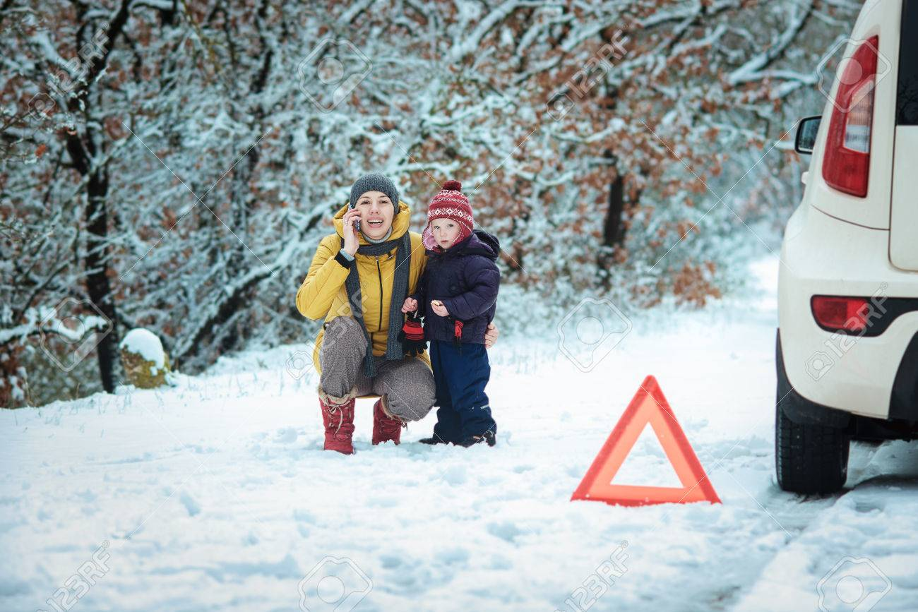 woman with a child on the winter road. emergency sign - 36813069