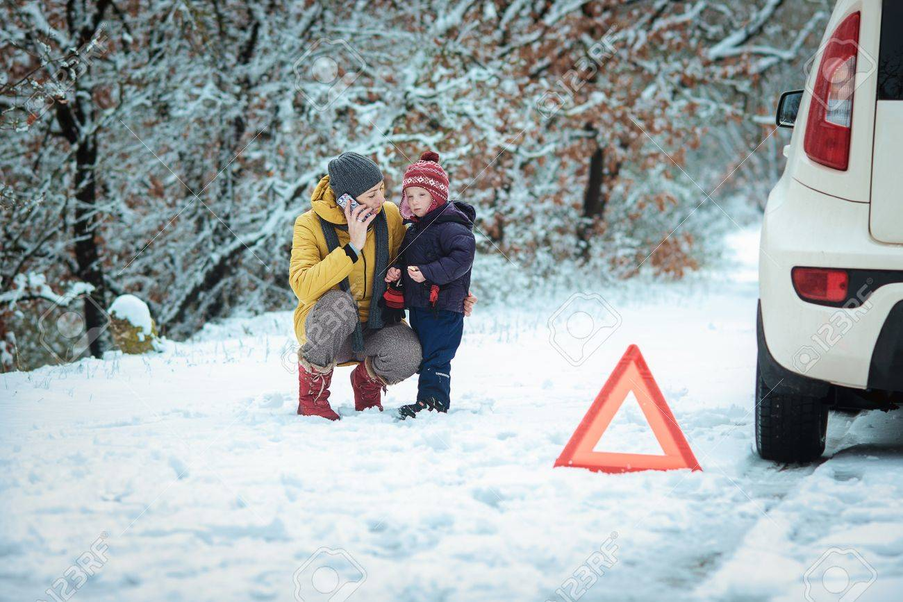 woman with a child on the winter road. emergency sign - 36813296