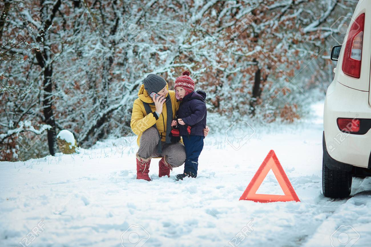 woman with a child on the winter road. emergency sign - 36813298