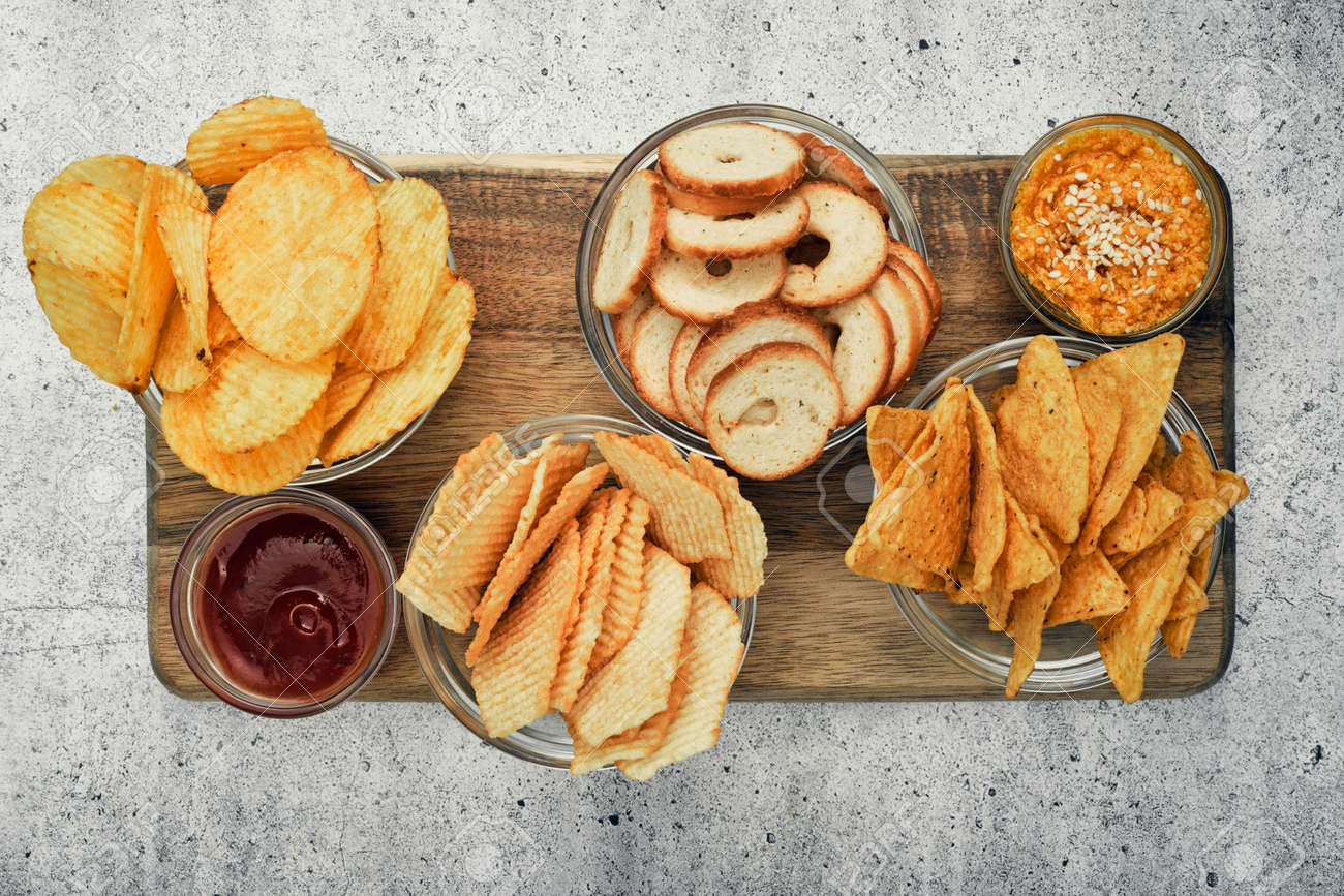 Mix of chips, snacks and crackers on a wooden stand. Unhealthy food, beer snack, ready meal. Close Up. - 150800402