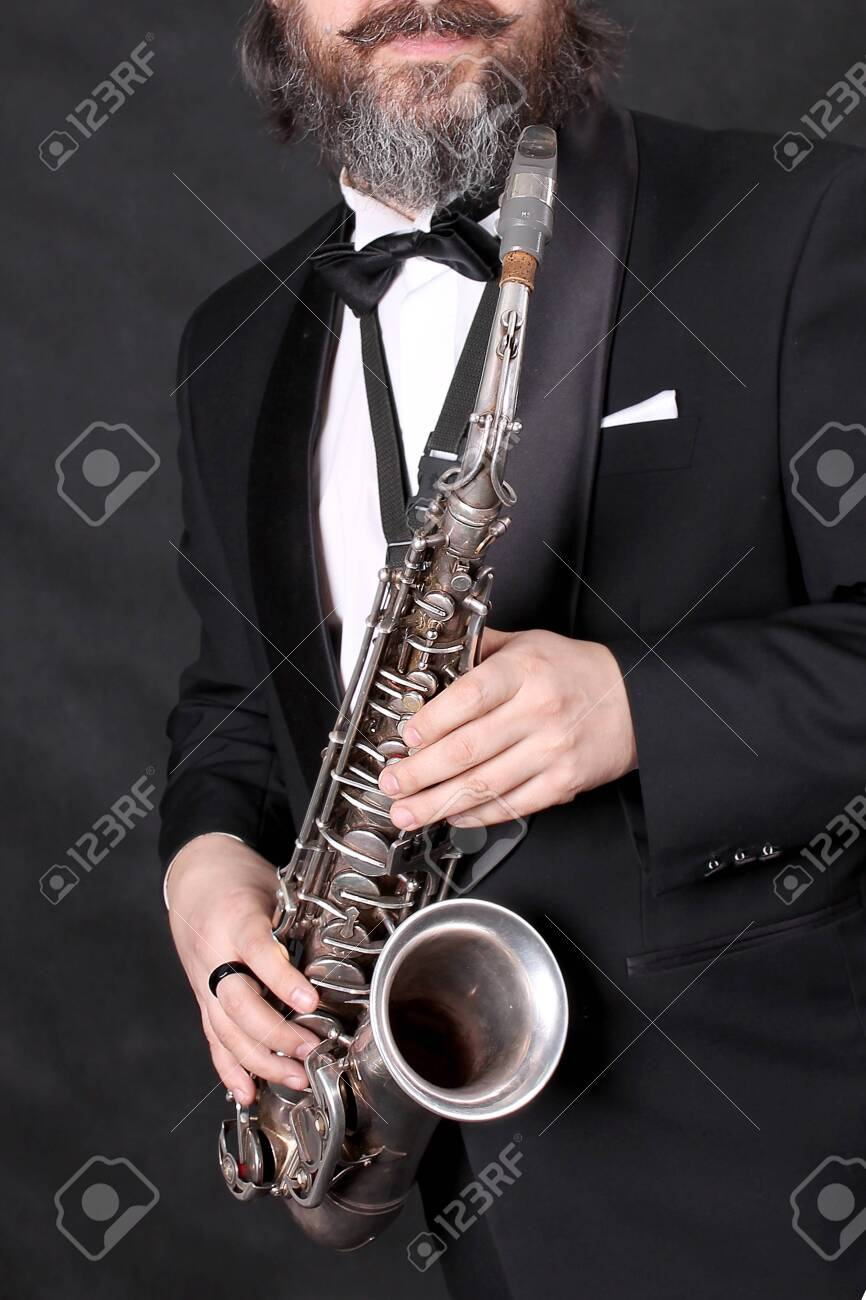 A male artist musician in a classic black suit, tailcoat, statuesque in a bow tie with a beard plays music on a gold saxophone.black background - 138257757
