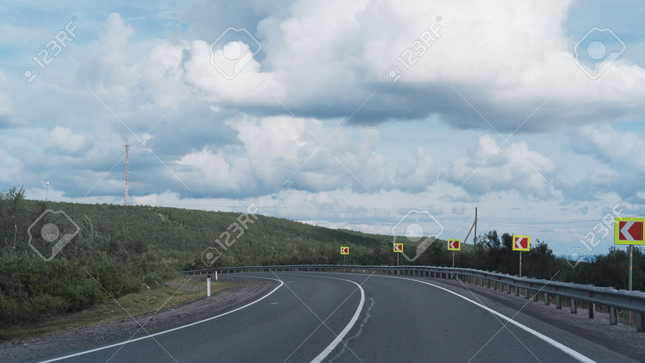 Highway or asphalt road through the forest. An empty roadway. Travel to natural places or reserves. - 165566670