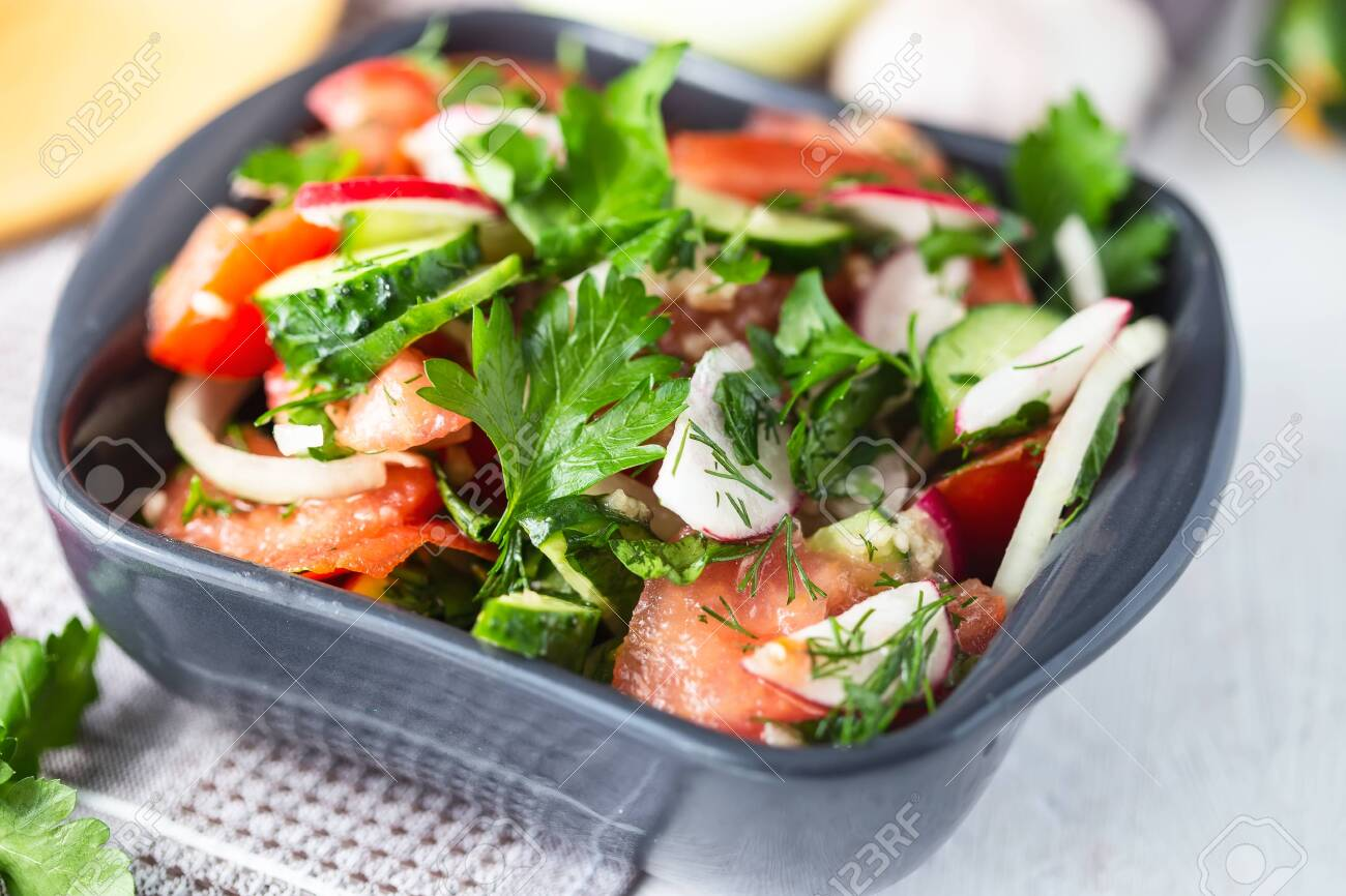 vegetarian salad of spring vegetables. tomatoes, cucumber, radish, onions. Dietary dish on a bright table. - 122386931
