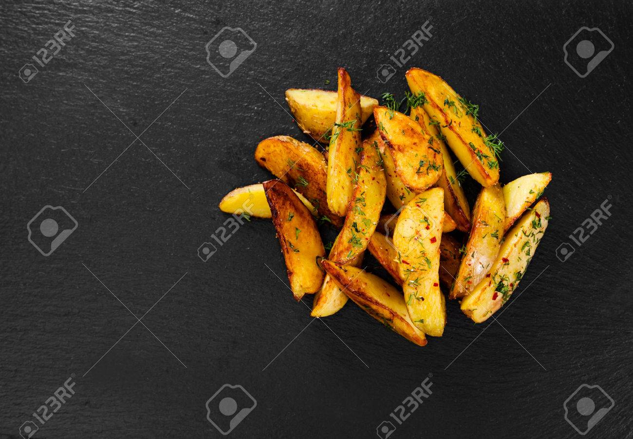 Potato wedges on black background. Top view. - 53723914