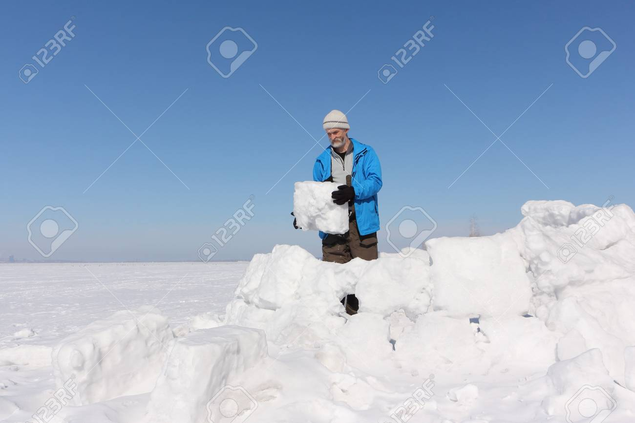 Man in a blue jacket building an igloo on a glade in the winter