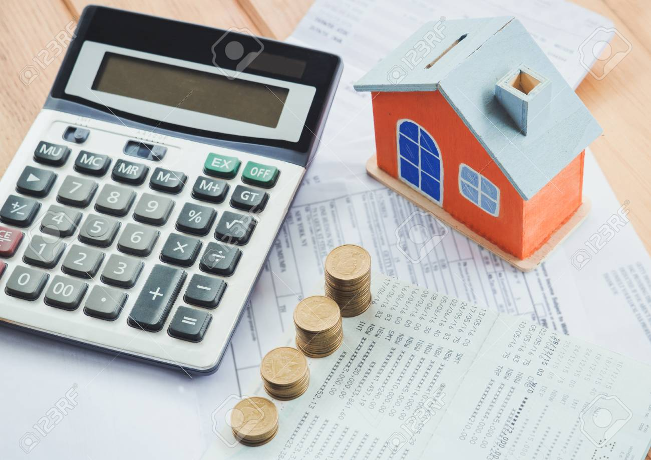 house model and coin on bank account calculator on table for