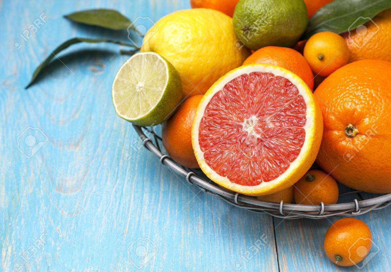 Different fresh citrus fruit in a basket on a blue wooden background - 51790772