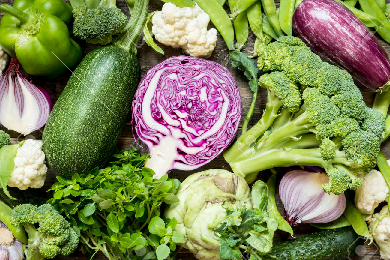 Top view set raw of green, red and purple vegetables spread on dark wooden background - 153474575
