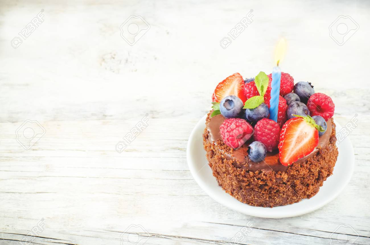 Chocolate Birthday Cake With Candle Raspberries Blueberries And Strawberries On A White Wood Background