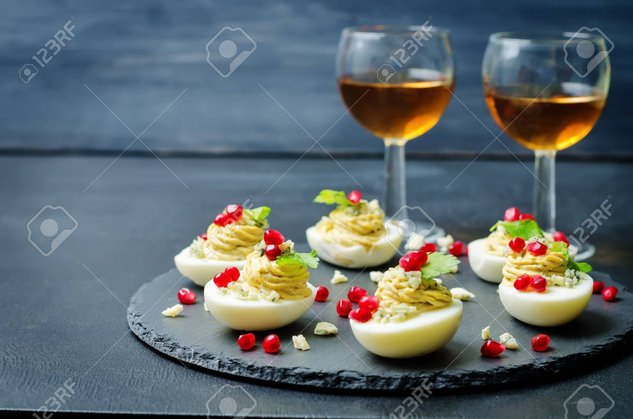 Blue cheese deviled eggs with pomegranate and fresh parsley leaves. toning. selective Focus - 124800502