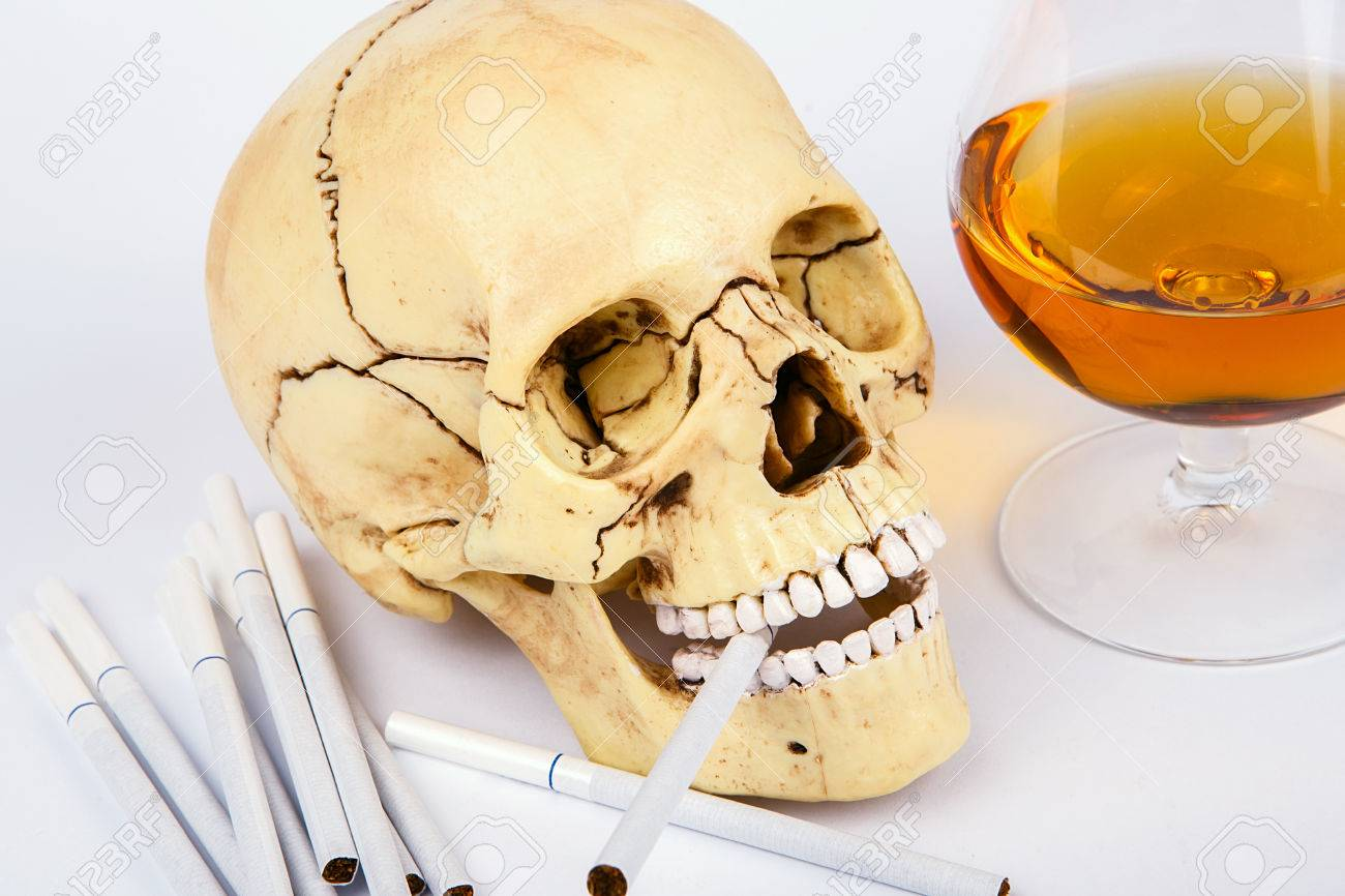 Human Skull Head With Cigarettes And Alcohol On White Background